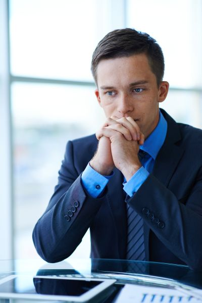 Sad businessman sitting at workplace and trying to find solution of problem